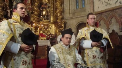 Cerimônia de beija-mãos do Padre Stefano Carusi (centro) e do então Diácono Raffray, à direita do padre.