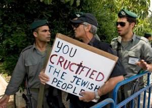 Ativista de extrema-direita é abordado em frente à residência presidencial em Jerusalém, nesta segunda-feira (11), quando protestava contra a visita do Papa Bento XVI a Israel. 'Você crucificou o povo judeu', diz o cartaz. (Foto: AP)