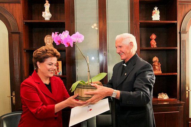 Dilma Roussef é recebida com flores por Dom Moacyr José Vitti, seu bispo auxiliar Dom Rafael Biernaski e o arcebispo emérito, Dom Pedro Fedalto, na Cúria de Curitiba. Agradecimento ao leitor Marcos Mattke pelo envio da foto.