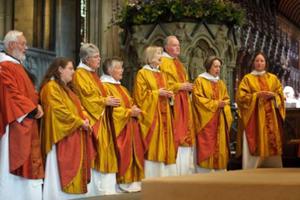 Um grupo de homens e mulheres recebendo as ordenações inválidas.