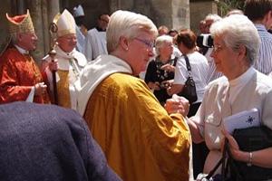 """Uma mulher revestida de casula. Ao fundo, Dom Nourrichard, bispo de Évreux, ao lado do """"bispo"""" de Salisbury."""
