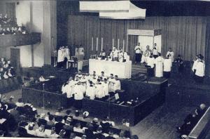 Missa Solene Coram Episcopo celebrada (verus populum) durante a Oitava Semana Litúrgica Nacional em Portland,1947. O Arcebispo E.D. Howard está no trono; à sua direita, o Reverendíssimo Joseph Gilmore, Bispo de Helena; à sua esquerda está o Reverendíssimo Francis Carroll, Bispo de Calgary.