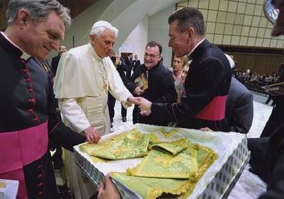 Recebidos pelo Papa Bento XVI após uma audiência geral, os superiores do Instituto Cristo Rei e Soberano Pontífice presenteiam o Santo Padre com um jogo de paramentos confeccionado na Bavária, sua terra natal. Fonte: The New Liturgical Movement.