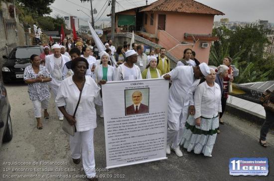 """Sincretismo: Numa """"caminhada"""" dentro da programação do evento, carregam cartaz  em homenagem a Zélio Fernandino de Moraes, a quem se atribuir a fundação da Umbanda em 15 de novembro de 1908."""