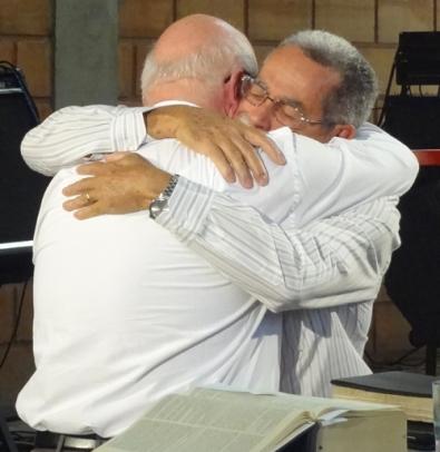 """Dom Francisco Biasin e Pastor Jamê Nobre se abraçam. """"Em algumas circunstâncias peculiares, como por ocasião das orações prescritas «pro unitate» em reuniões ecuménicas, é lícito e até desejável que os católicos se associem aos irmãos separados na oração"""". (Unitatis Redintegratio, 8)"""