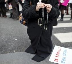 """Instituto Civitas: mulher reza o terço antes do início da manifestação. No chão, o cartaz: """"A família é sagrada!""""."""