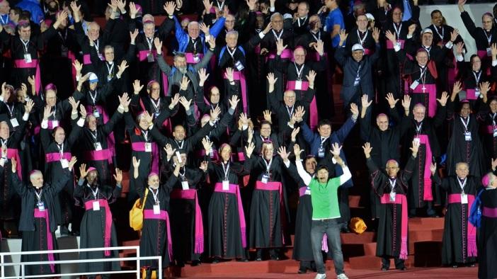 """Noite do dia 27: Bispos em momento de descontração atendem ao apelo de um jovem instrutor para que também participem do maior flash mob já realizado no planeta. Na manhã seguinte, minutos antes da Missa de Envio, a dança seria repetida não só pelos leigos, mas também por vários sacerdotes devidamente paramentados. Como diz o ditado: """"Quem está na chuva é pra se molhar.""""."""