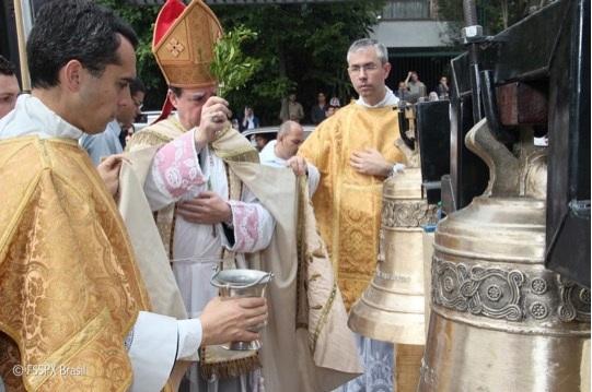 Dom Alfonso de Galarreta asperge os novos sinos, acompanhado dos sacerdotes do priorado.
